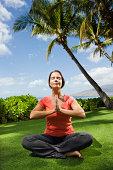 Woman meditating by palm tree, Maui, Hawaii