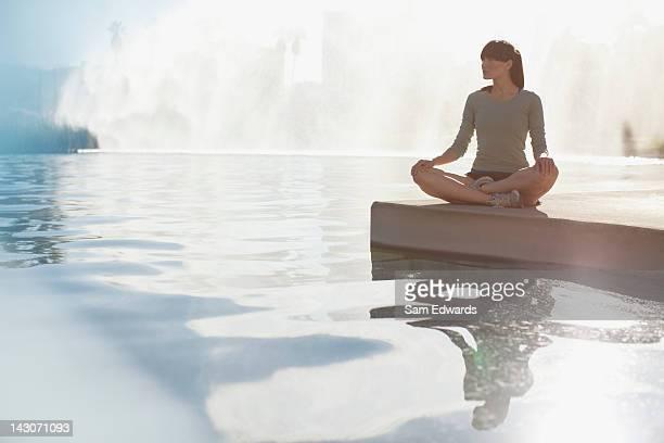 Woman meditating by still pool