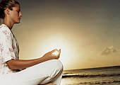 Woman Meditating by the Sea at Sunset