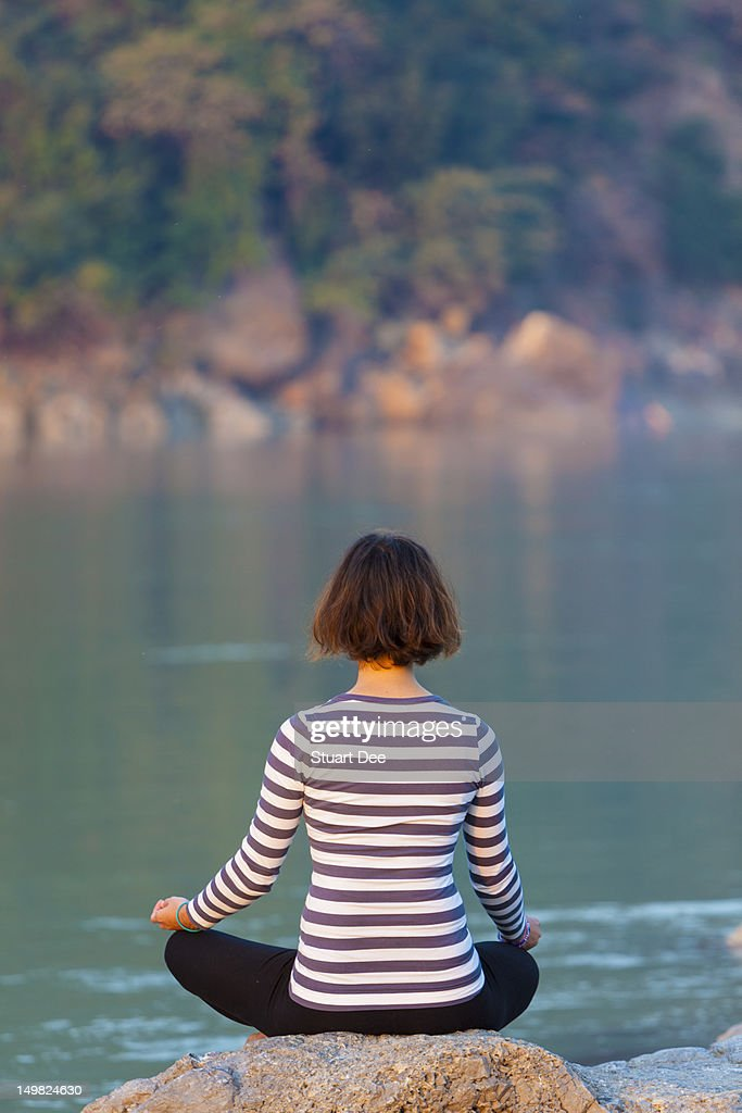 Woman meditating / doing yoga outdoors : Stock Photo