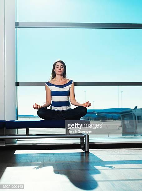 Woman Meditating in Airport