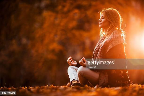 Frau Meditieren im Herbst Tag.