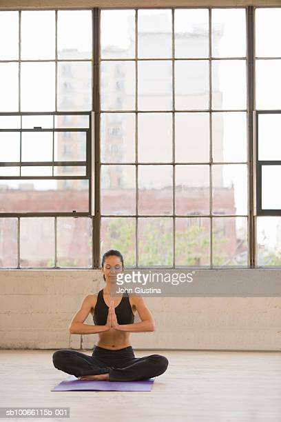 Woman meditating in empty warehouse