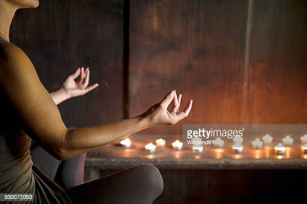 Woman meditating in wooden house