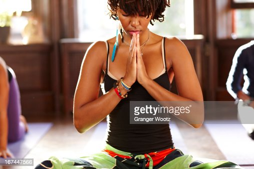 Woman meditating in yoga class : Stock Photo
