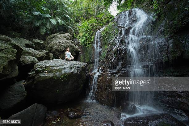 Woman meditating in Yoga pose by jungle waterfall