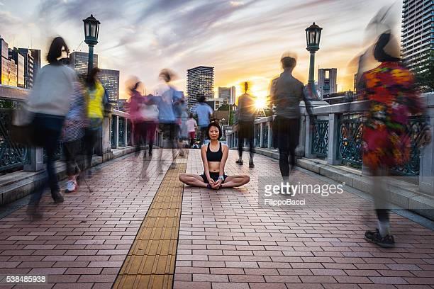 Mujer Meditando en la multitud al anochecer