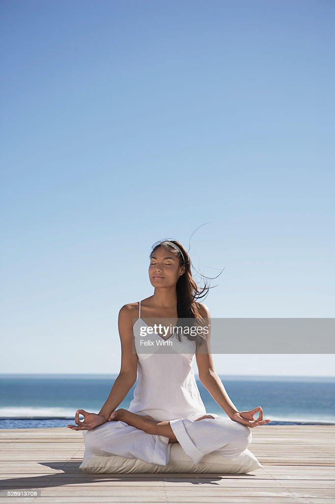 Woman meditating near ocean : Bildbanksbilder