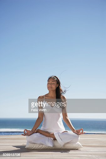 Woman meditating near ocean : Bildbanksbilder