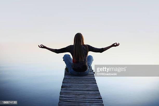 Woman meditating on a beach dock