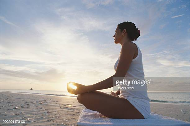 Woman meditating on beach, sun shining through fingers, side view