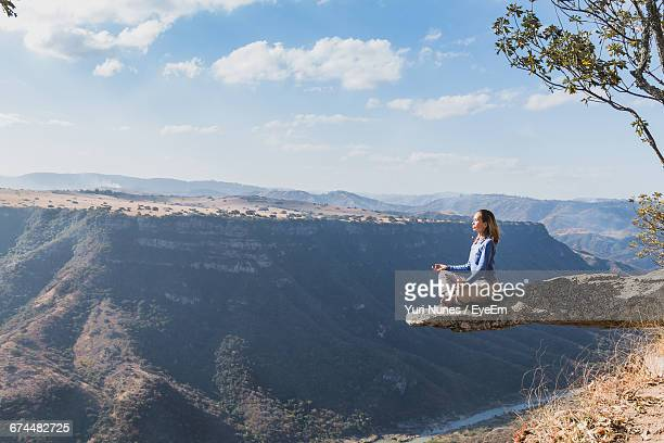 Woman Meditating On Cliff By Mountains Against Sky