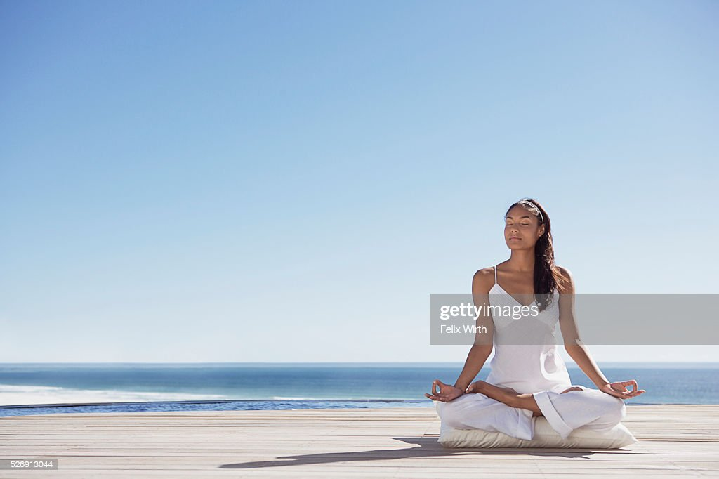 Woman meditating on deck near ocean : Foto de stock