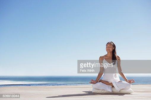 Woman meditating on deck near ocean : ストックフォト