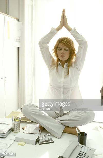 Woman meditating on desk in office