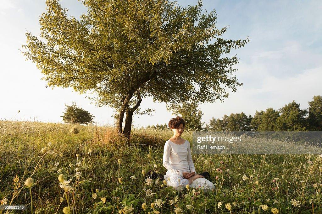 Woman meditating on grassy field : Stock Photo