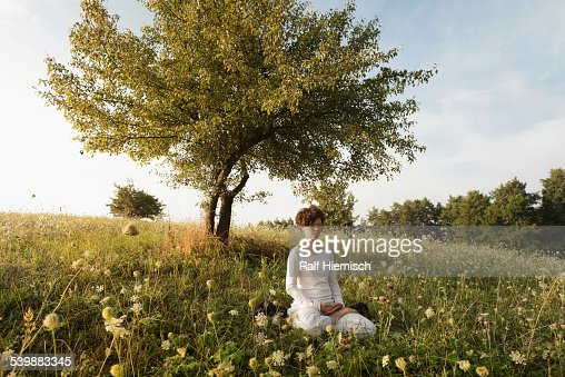 Woman meditating on grassy field