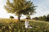 Woman meditating on grassy field