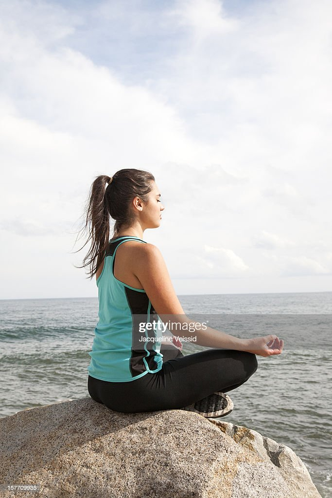 Woman meditating on rock overlooking ocean : Stock Photo