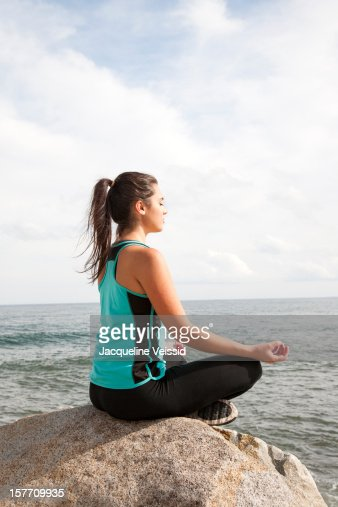 Woman meditating on rock overlooking ocean : Stock Photo
