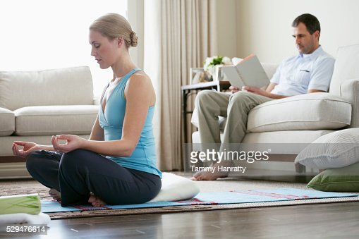 Woman meditating while husband reads : Stock Photo