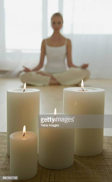 Woman meditating with candles