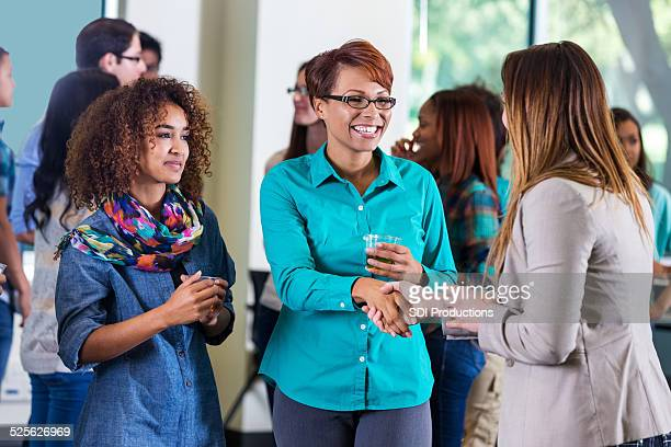 Woman meeting daughter's professor during college orientation mixer