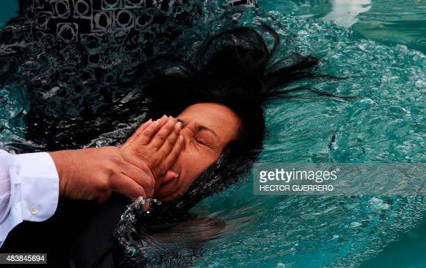 A woman member of the Light of the World church is immersed in water for the celebration of baptism in Guadalajara City on August 13 within the...