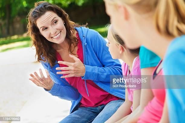 Frau mentoring Gruppe von Mädchen im park