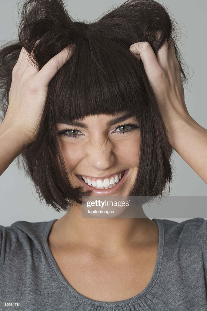 Woman messing up hair : Stock Photo