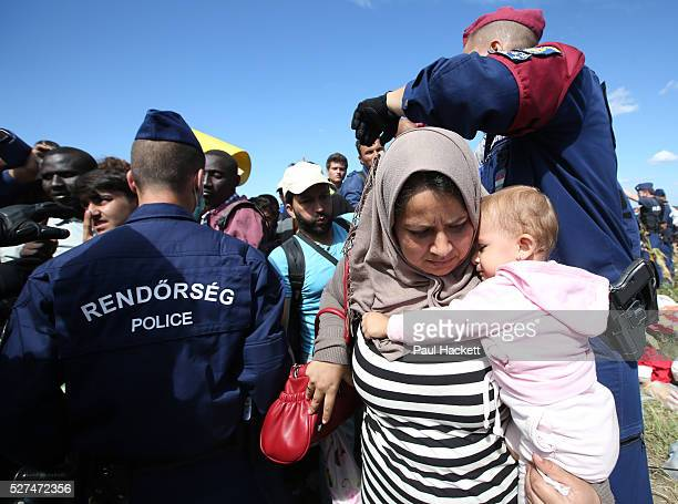 A woman migrant and her baby break through a police corden to board a bus close to the Hungarian and Serbian border town of Roszke Hungary September...