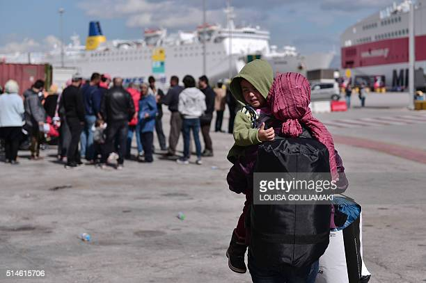 A woman migrant carrying her son in the port of Piraeus on March 10 waits to be transferred to a refugee camp in central Greece with other migrants...