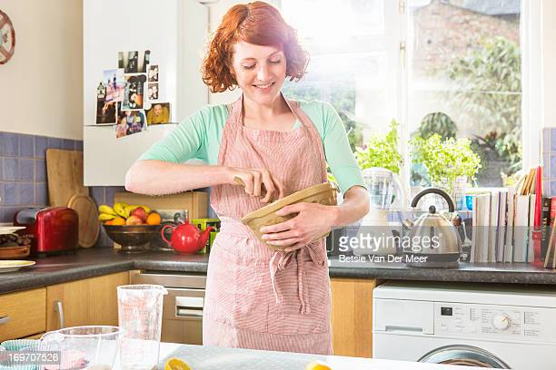 Woman mixing ingredients in bowl in kitchen.