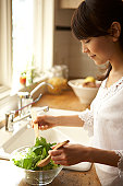 Woman mixing salad in kitchen, close-up