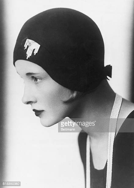 A woman modeling a hat fitted with a brooch on the front and a bow on the nape of the neck Ca 19251932