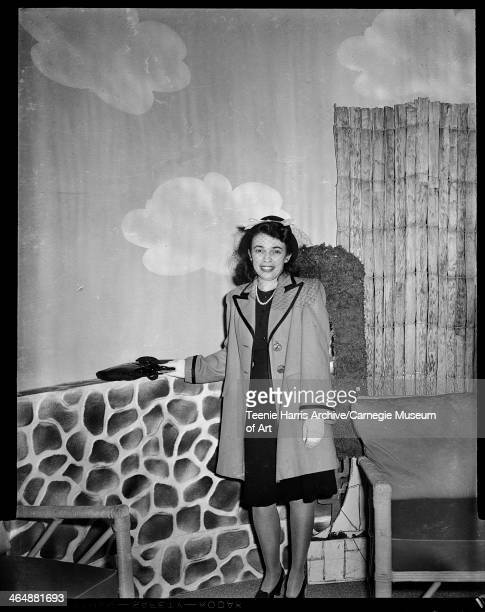 Woman modeling dark dress light colored coat with dark trim and veil over face posed in front of painted stone wall for benefit fashion show in May...
