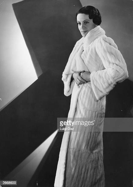 A woman modelling a full length white ermine fur coat designed by Max