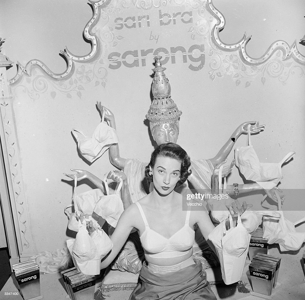 A woman modelling a 'Sarong' brand sari bra whilst holding one on in each of her outstretched hands. She is standing in front of an effigy of an multi-armed Hindu goddess toting a bra in each hand.
