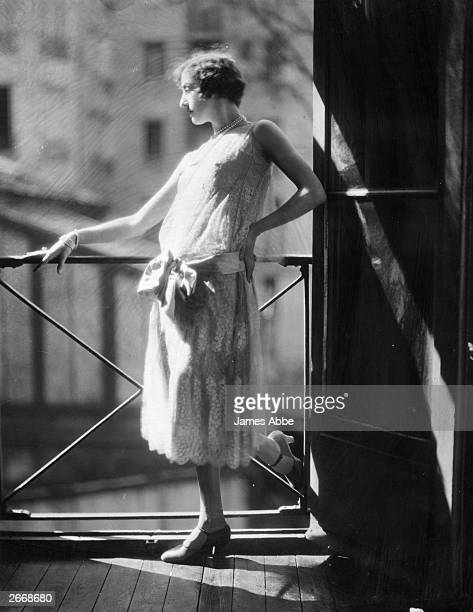 A woman modelling a typically twenties style grey silk and lace dress with a bow sash around the dropped waist line