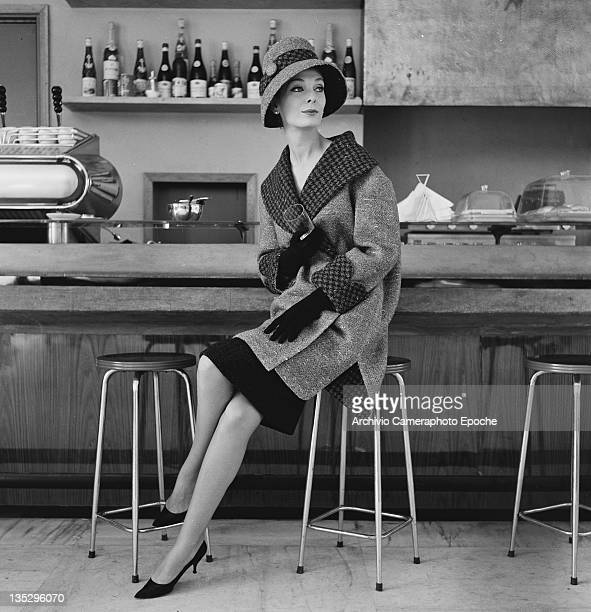 A woman modelling a winter coat with houndstooth trim and matching hat Rome circa 1957