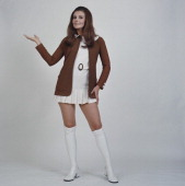 A woman modelling women's fashions in a studio portrait wearing a white mini dress with a brown jacket white shoes and white kneehigh socks circa 1960