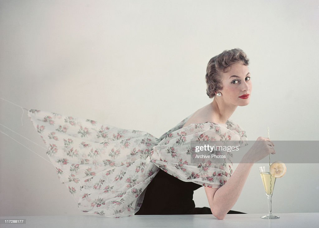 A woman modelling women's fashions in a studio portrait, wearing a white floral print shawl over a black dress while posing with a wine glass, circa 1960. The shawl is extended out behind the model.