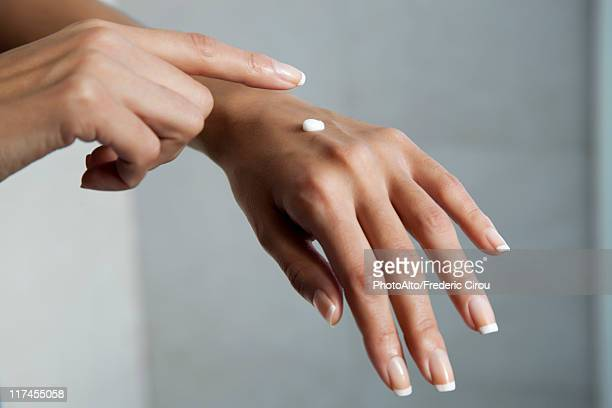 Woman moisturizing hands, cropped