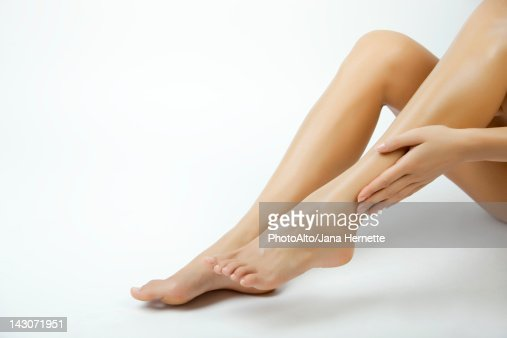 Woman moisturizing legs, cropped