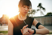 Close up shot of young sportswoman looking at smartwatch. Fitness female monitoring her progress on smartwatch.