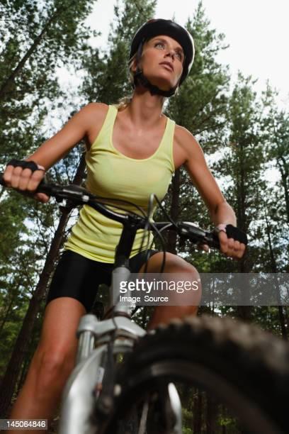 Woman mountain biking in forest