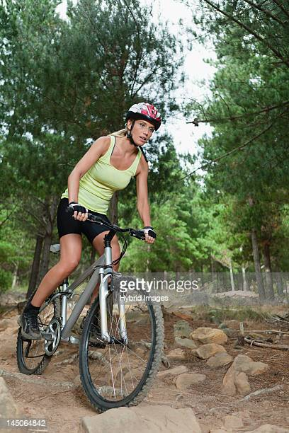 Woman mountain biking on rocks