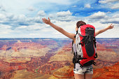 happy woman with backpack raised arm hands and looking to sky in grand canyon. asian