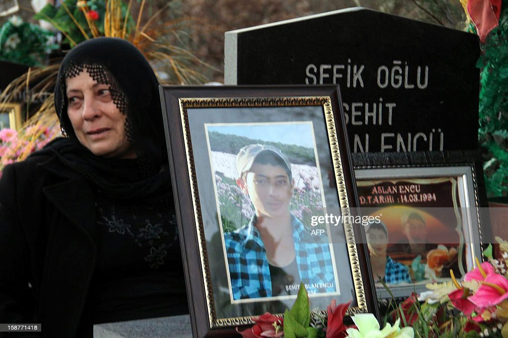 A woman mourns for a victim of a Turkish air raid, at the cemetery of Gulyazi Village on December 28, 2012 on the first anniversary of a Turkish military air strike aimed at Kurdish rebels that killed 34 civilians working as smugglers at the Turkey-Iraq border in Sirnak.