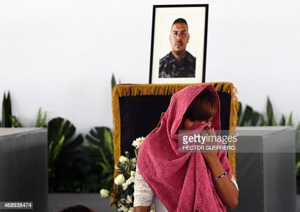 A woman mourns next to one of the 15 coffins of police members of the State of Jalisco killed during an ambush by criminal gang assassins on April 6...